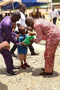 Photo de la remise d'un kit scolaire à un petit garçon de Makénéné