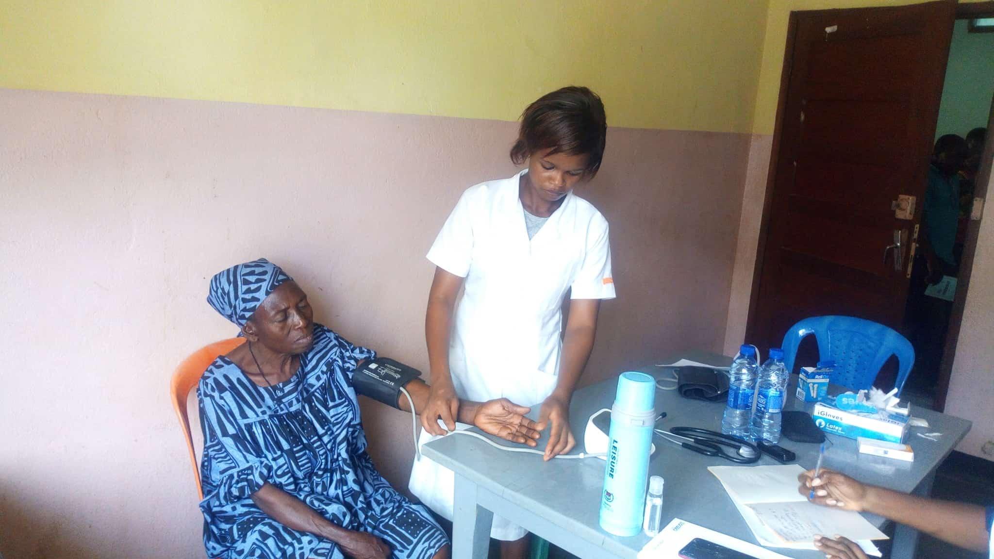 Photo d'une femme qui prend la tension d'une patiente durant une Journée Médicale de Makénéné