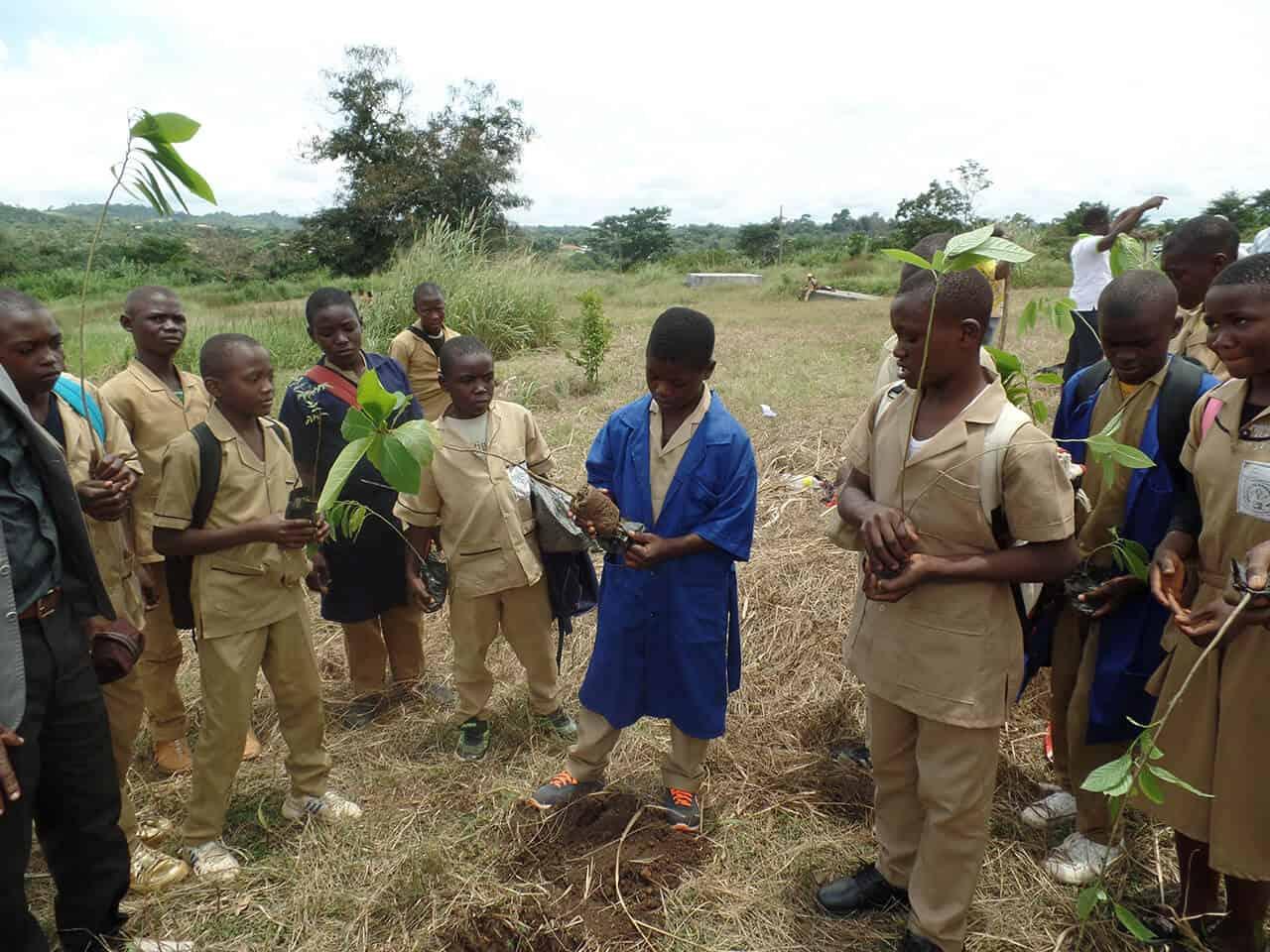 Photo de plusieurs jeunes qui plantent des arbres devant des écoliers dans le cadre du projet de reboisement dans les établissements scolaires